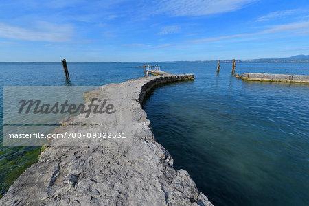 Stone harbor wall with a pier on Lake Garda at Punta San Vigilio in Garda, Veneto, Italy