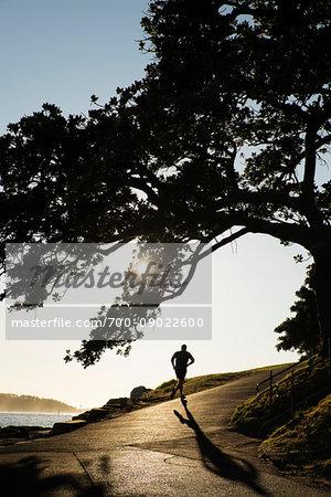 Silhouette of backview of man jogging uphill along the shoreline of Sydney Harbour in Sydney, Australia