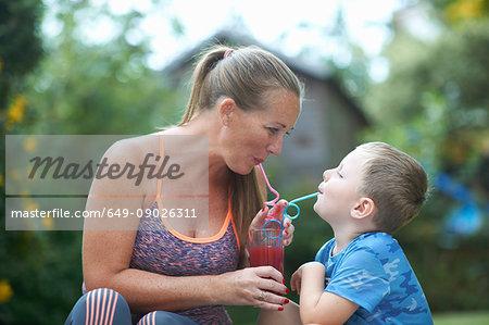 Boy and mother sharing fresh smoothie in garden