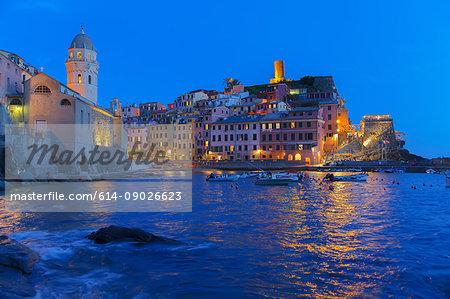 Cliff side fishing village illuminated at dusk, Vernazza, Liguria, Italy, Europe