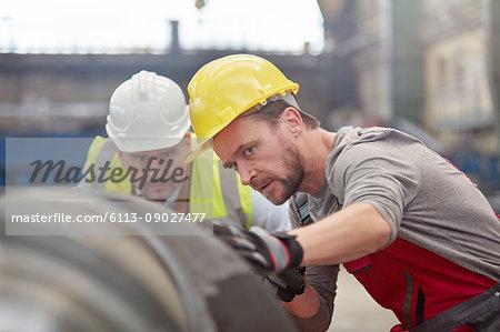 Focused male engineers examining steel part in factory