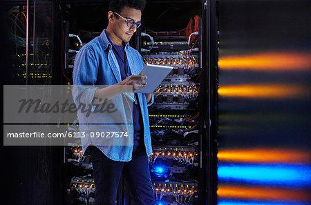 Focused male IT technician using digital tablet at panel in dark server room