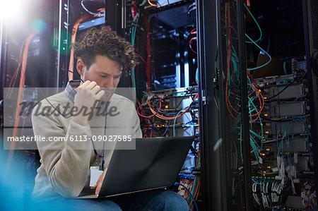 Focused male IT technician using laptop in server room