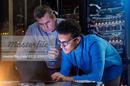 Focused male IT technicians working at laptop in dark server room
