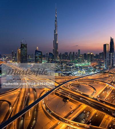 Cityscape of Dubai, United Arab Emirates at dusk, with the Burj Khalifa skyscraper and illuminated highways in the foreground.