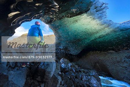 Skaftafell national park, Iceland, Europe. Man admire the blue crystal ice cave under the Vatnajokull glacier in winter.