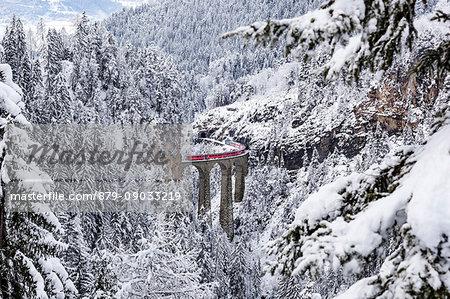 The Bernina Express red train as it passes over the Landwasser bridge, Filisur, Graubunden, Switzerland, Europe.