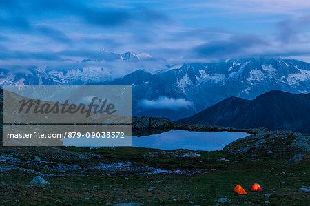 Strino lakes, Stelvio National park, Trento province, Trentino Alto Adige, Italy. Two tents and the Presanella's range at twilight.