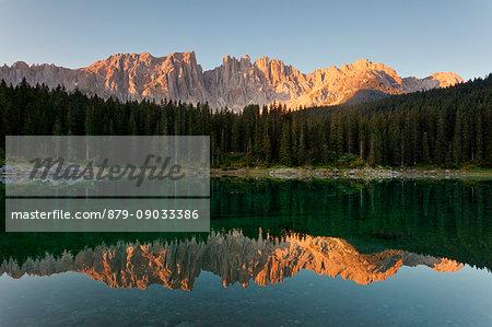 Carezza lake, Dolomites, Trentino-Alto Adige, Italy. Latemar group are reflected into the Carezza's lake in the sunrise