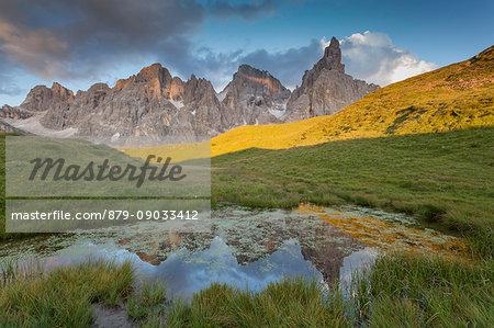 Baita Segantini, Pale of San Martino, Trento province, Dolomites, Trentino Alto Adige, Italy, Europe. Cimon della Pala reflected into a small lakes at sunset.