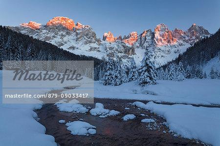 Venegia valley, Paneveggio Pale di San Martino Natural Park, Trentino Alto Adige, Italy, Europe. Winter in Venegia valley at sunset. Travignolo river and Pale di San Martino at sunset in winter