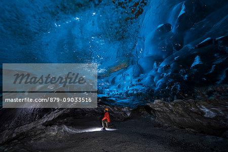 Man inside an ice caver under the Vatnajokull glacier, Vatnajokull national park, East Iceland, Iceland (MR)