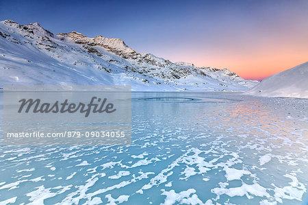 Surface of Lake Bianco of Bernina enhanced by soft colors of dawn. Canton of Graubunden. Engadine. Switzerland. Europe