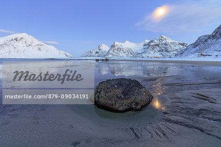 Full Moon reflected in the icy sea around the surreal Skagsanden beach Flakstad Nordland county Lofoten Islands Norway Europe
