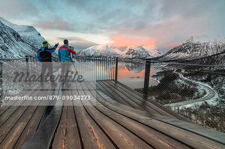 Photographers on platform admire the snowy peaks reflected in sea at sunset Bergsbotn Senja Troms County Norway Europe