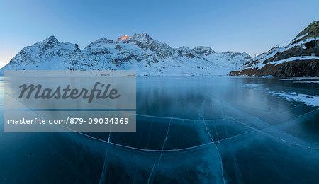 Panorama of frozen Lago Bianco surrounded by snowy peaks at dusk Bernina Pass canton of Graubünden Engadine Switzerland Europe