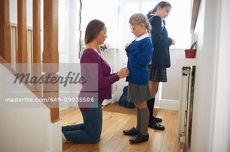 Woman fastening daughter's school cardigan in hallway