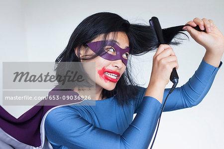 Woman dressed as superhero straightening hair against gray background