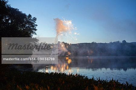 Fireworks exploding over lake