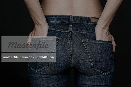 Woman wearing jeans, hands in back pockets