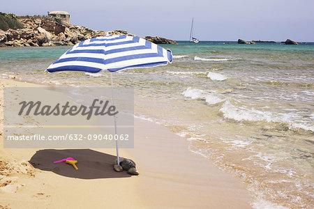 Parasol on beach near water's edge