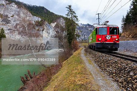 The Red Train passes along the Rhine River. Rhein Gorge(Ruinaulta), Flims, Imboden, Graubunden, Switzerland, Europe