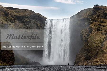 Man staring at Skogafoss waterfall, Skogar, Gardabaer, Capital Region, Iceland, Europe