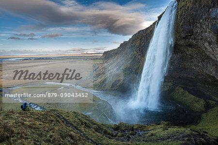 Photographer taking pictures of Seljalandsfoss waterfall, Porsmerkurvegur, Sudurland, Iceland, Europe