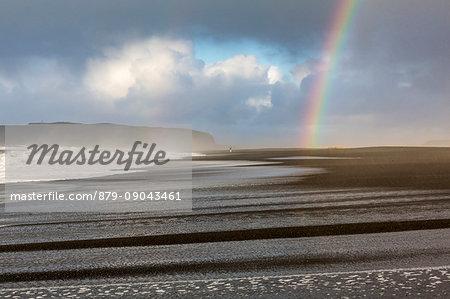 A man is walking towards the rainbow on the beach of Reynisfjara, Vik, Sudurland, Iceland, Europe