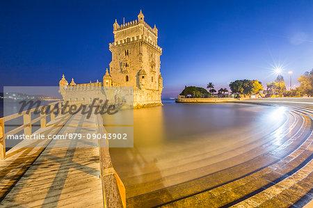 Blue dusk and lights on the Tower of Belém reflected in Tagus River Padrão dos Descobrimentos Lisbon Portugal Europe