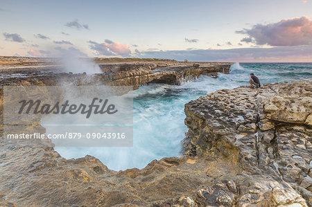 Hiker on the cliffs admires the crashing waves at Devil's Bridge Caribbean Antigua and Barbuda Leeward Islands West Indies