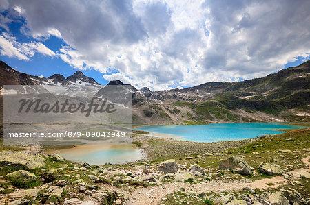 Clouds and sun on turquoise lakes framed by rocky peaks Joriseen Jörifless Pass canton of Graubünden Engadin Switzerland Europe