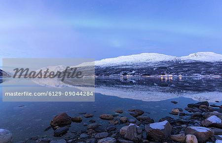 The Northern Lights appear in the sky during twilight. Skarvdalen, Kafjord, Lyngen Alps, Troms, Norway, Lapland, Europe.