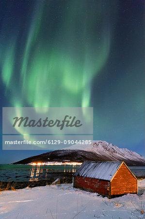 The Northern Lights paints the sky above the Nature Reserve Spaknesora. Spaknesora naturreservat, Djupvik, Lyngenfjord, Lyngen Alps, Troms, Norway, Lapland, Europe.