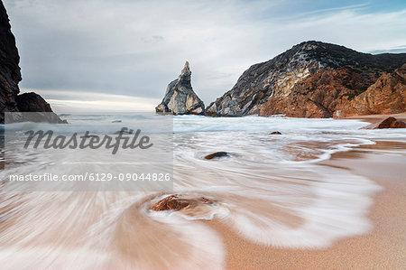 Ocean waves crashing on the sandy beach of Praia da Ursa surrounded by cliffs Cabo da Roca Colares Sintra Portugal Europe