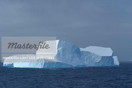 Sunlit iceberg in the dark blue waters of the Antarctic Sound at the Antarctic Peninsula, Antarctica