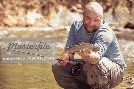 Fisherman holding caught fish in river, Mozirje, Brezovica, Slovenia