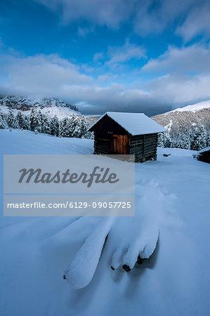 Wooden lodge covered in snow. Passo delle Erbe, Bolzano, Trentino Alto Adige - Sudtirol, Italy, Europe.