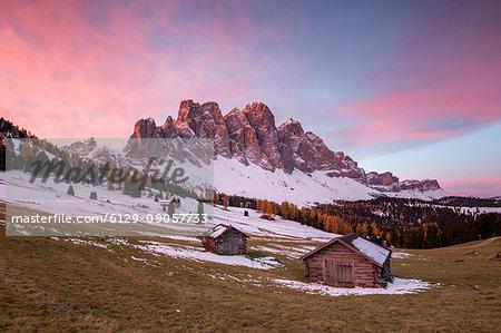Sunrise with two wooden lodges and Odle Dolomites. Malga Gampen, Funes, Bolzano, Trentino Alto Adige - Sudtirol, Italy, Europe.