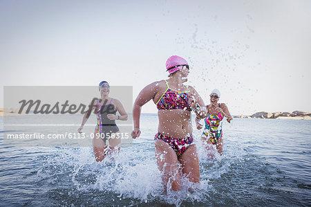 Female open water swimmers running, splashing in ocean surf