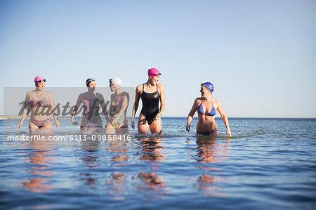 Female open water swimmers walking, wading in sunny ocean