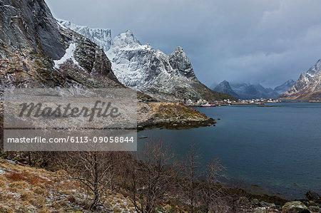 Snowy, rugged mountains along water, Reine, Lofoten, Norway