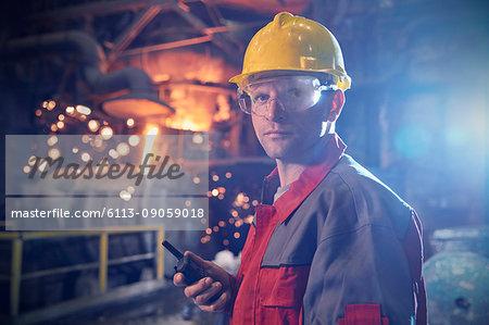 Portrait confident, serious steelworker with walkie-talkie in steel mill