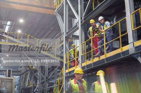Steelworkers talking on platform in steel mill
