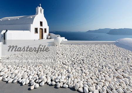 Small whitewashed church against blue sea and sky, Finikia, near Oia, Santorini, Cyclades, Greek Islands, Greece, Europe