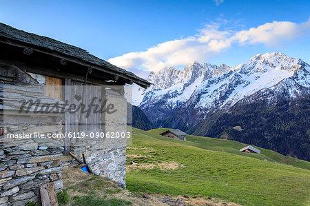 Alpine hut framed by meadows and snowy peaks at dawn, Tombal, Soglio, Bregaglia Valley, canton of Graubunden, Switzerland, Europe