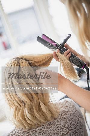 Hairdresser straightening woman's hair in hair salon