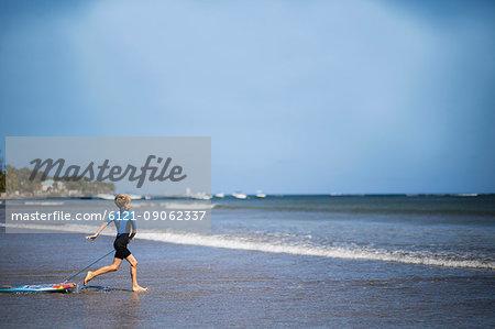 Boy running with surfboard into sea