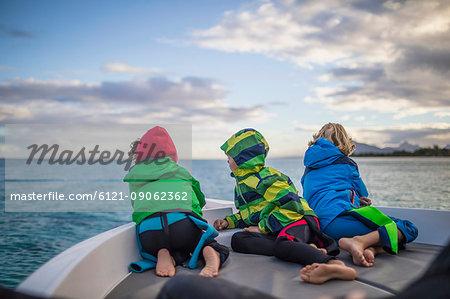 Children admiring seascape from boat