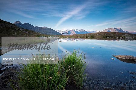 The clear sky is reflected in the blue alpine lake, Muottas Muragl, Samedan, Canton of Graubunden, Engadine, Switzerland, Europe